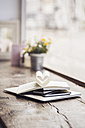 Book with heart-shaped pages on stack of mobile devices - KNSF000244