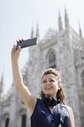 Italy, Milan, tourist taking selfie with cell phone in front of cathedral - MAUF000800