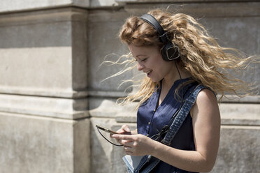 Smiling young woman with headphones looking at her smartphone - MAUF000806