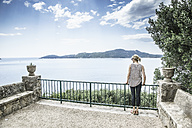 Croatia, Trsteno, back view of woman standing on a terrace looking to the sea - CHPF000256