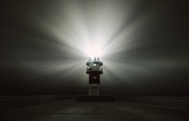 Spain, Carino, beaming lighthouse in a foggy night - RAEF001407