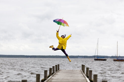 Germany, Steinhuder Meer, woman wearing yellow rain coat and Wellington boots jumping in the air - KLRF000463