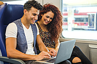 Smiling young couple in a train using laptop - SIPF000766