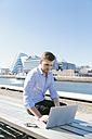 Ireland, Dublin, young businessman sitting on bench using laptop - BOYF000526