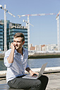 Ireland, Dublin, smiling young businessman sitting on bench with laptop telephoning with cell phone - BOYF000529