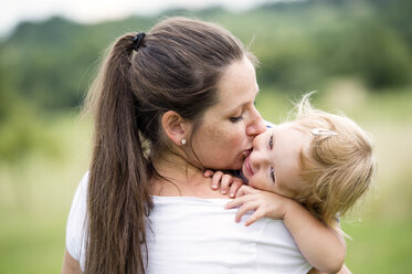 Mother kissing at hugging her little daughter - HAPF000721