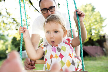 Father pushing daughter on swing in park - HAPF000736
