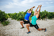 Couple doing pilates in a vineyard - KIJF000727