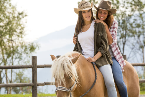 Young women riding on a horse at riding stable - ZOCF000135