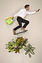 Skateboarding bussinessman in nature with shopping bags and smartphone - BAEF001190