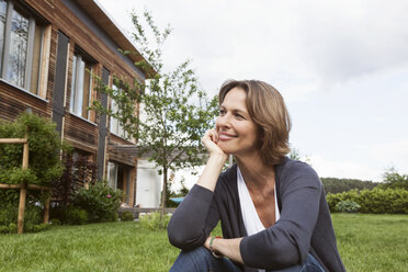 Smiling woman relaxing in garden - RBF004837