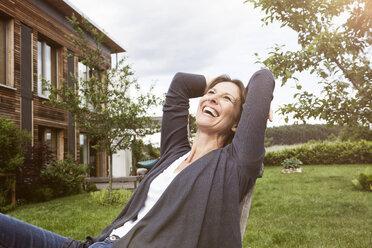 Laughing woman relaxing in garden - RBF004840