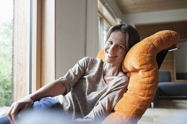Smiling woman relaxing in armchair - RBF004843