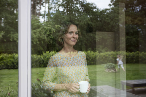 Smiling woman holding cup looking out of window - RBF004846