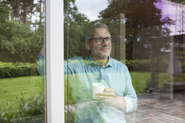Smiling man holding cup looking out of window - RBF004852