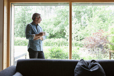Mature man holding cup looking out of window - RBF004855