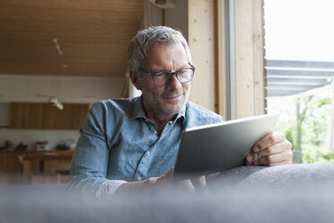 Mature man using digital tablet on couch - RBF004858