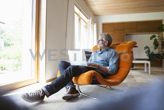 Mature man using laptop in armchair - RBF004861 - Rainer Berg/Westend61