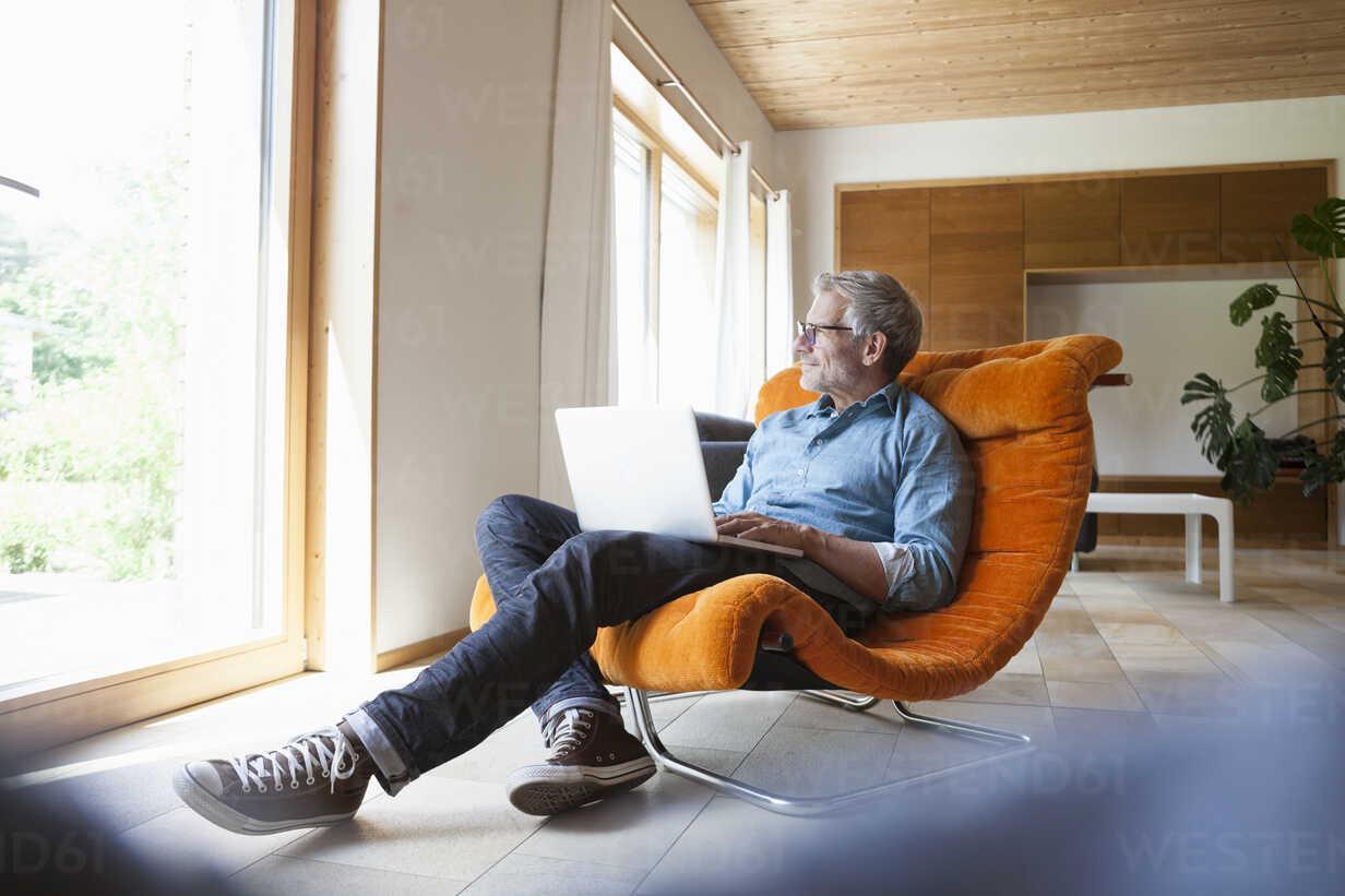 Mature man using laptop in armchair - RBF004861 - Rainer Berg/Westend61