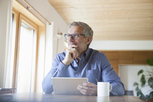 Mature man using digital tablet on table at home - RBF004864