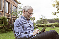 Mature man using digital tablet in garden - RBF004870
