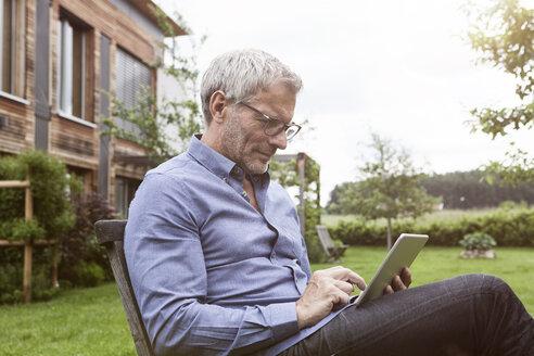 Mature man using digital tablet in garden - RBF004870