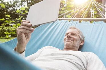 Mature man using digital tablet in hammock - RBF004873