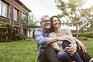 Happy mature couple sitting in garden - RBF004882