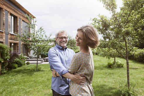 Happy mature couple dancing in garden - RBF004888