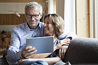 Mature couple sharing digital tablet on couch - RBF004891