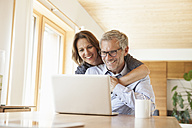 Happy mature couple sharing laptop at home - RBF004894