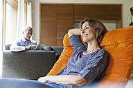 Smiling woman relaxing in armchair with husband in background - RBF004900