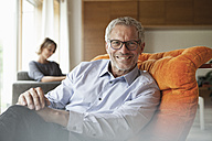Smiling man relaxing in armchair with wife in background - RBF004906
