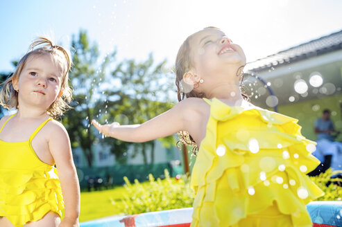 Two little sisters in paddling pool in the garden - HAPF000757