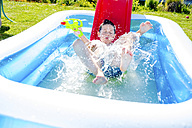 Little boy sliding into paddling pool - HAPF000760