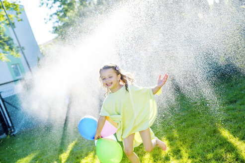 Little girl having fun with lawn sprinkler in the garden - HAPF000769