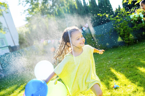 Little girl with balloons having fun with lawn sprinkler in the garden - HAPF000772