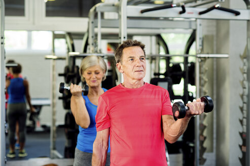 Senior man and mature woman working out in fitness gym - HAPF000781