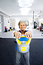 Mature woman lifting kettlebell in fitness gym - HAPF000784