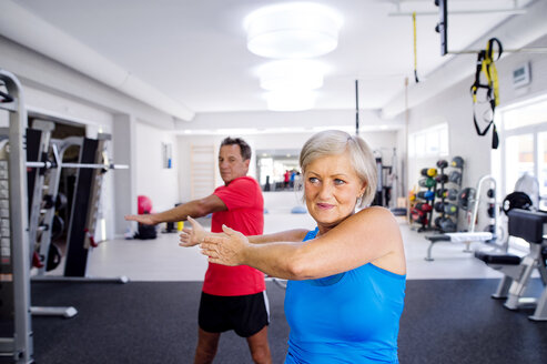 Mature woman and senior man doing gymnastics in fitness gym - HAPF000787