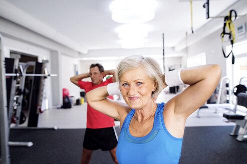 Mature woman and senior man doing gymnastics in fitness gym - HAPF000790