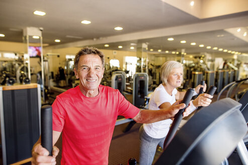 Senior man and mature woman on step machine in fitness gym - HAPF000823