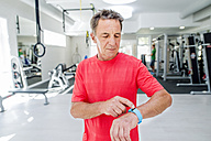 Senior man in fitness gym looking at smartwatch - HAPF000835