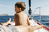 Little boy sitting on bow of sailing boat looking at distance - JRFF000829