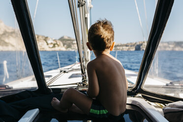 Back view of little boy sitting on a sailing boat - JRFF000832
