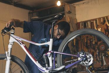 Mechanic in repair shop repairing bicycle - SKCF000168
