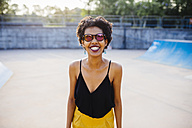 Portrait of smiling young woman in a skatepark wearing mirrored sunglasses - GIOF001402