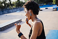 Smiling young woman with earphones dancing in a skatepark - GIOF001417