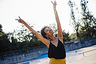 Happy young woman in a skatepark showing victory signs - GIOF001420