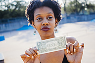 Portrait of woman showing one dollar banknote, close-up - GIO001426
